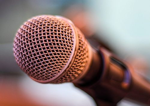 grey microphone on brown wooden stand